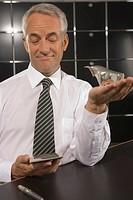 Businessman holding a bull figurine and a calculator