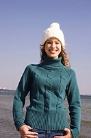 Young happy woman in winter hat on the beach