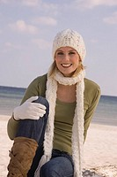 Portrait of young woman in winter clothing at the beach