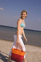 Young woman in bikini walking on the beach