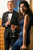 Portrait of a mature man and a young woman holding champagne flutes