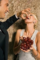 Side profile of a young man feeding red grapes to a young woman