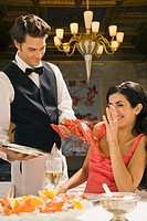 Waiter serving a lobster to a young woman