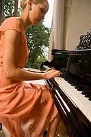 Side profile of a young woman playing a piano