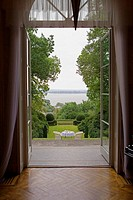 Table and two armchairs in a garden viewed through a door (thumbnail)