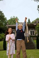 Boy and girl holding croquet mallets