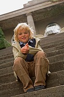 Portrait of a boy sitting on steps and smiling