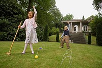Boy and girl playing croquet in a garden