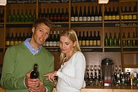Portrait of a man holding a wine bottle with a woman standing beside him in a bar