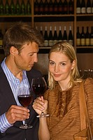 Mid adult couple holding glasses of red wine in a bar