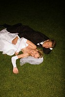 Portrait of a newlywed couple lying in a lawn and smiling