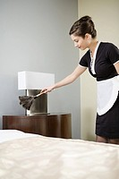 Maid dusting night stand