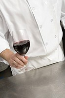 Chef holding glass of wine