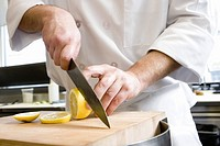 Male chef slicing lemon
