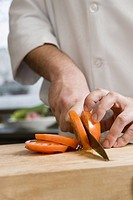 Male chef slicing tomato