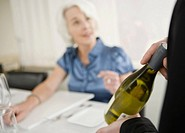 Waiter showing wine bottle to senior woman