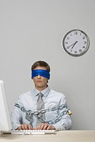 Businessman blindfolded and chained