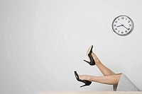 Businesswoman's legs under clock