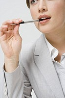 Businesswoman biting on pen