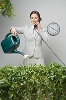 Businesswoman watering hedge