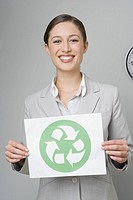 Businesswoman holding recycling sign