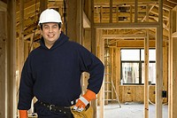 Male construction worker in front of heavy machinery