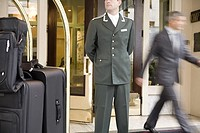 Bellhop standing next to luggage cart