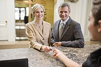 Couple paying at hotel front desk