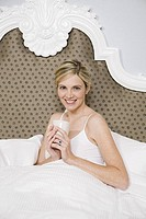 Woman holding coffee mug in bed