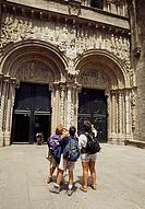 Three pilgrims looking at the Platerías portal of the cathedral, Platerías square, Santiago de Compostela. La Coruña province, Galicia, Spain