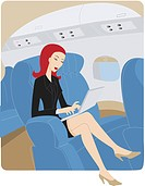 Businesswoman using a laptop while on an airplane