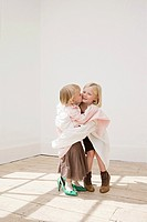 Two young sisters kissing (thumbnail)