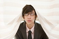 Young businessman under a sheet