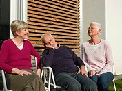 Senior friends resting on deckchairs