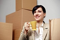 Businesswoman with coffee cup among boxes