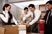 Four business people unpacking boxes in office