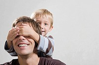 A son covering his fathers eye