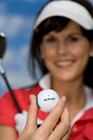 young woman with golf club and golf ball