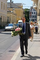 man with bouquets of flowers on street
