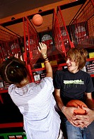 Teenage couple playing ball game in arcade (thumbnail)