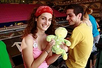 Teenage couple at game in amusement park (thumbnail)