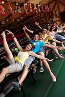 Teenagers posing in front of game in amusement park