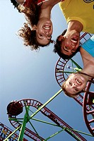 Teenagers posing at roller coaster at amusement park