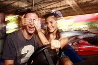 Teenage couple in bumper car in amusement park