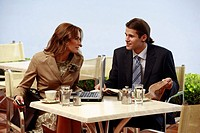 Business man and woman at cafe with laptop