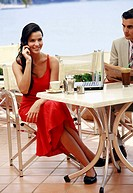 Woman at seaside cafe table with laptop (thumbnail)