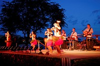 Hula dancers on stage at dusk after a luau in Maui