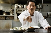 Asian male chef seasoning food