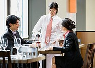 Asian female server pouring wine for diners