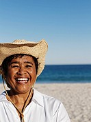 Mixed Race woman wearing straw hat (thumbnail)